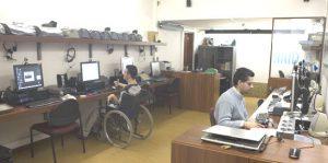Sala do NAID vista da porta da entrada com um rapaz deficiente motor a utilizar um computador do lado esquerdo da sala e um homem a utilizar um computador no lado direito da sala